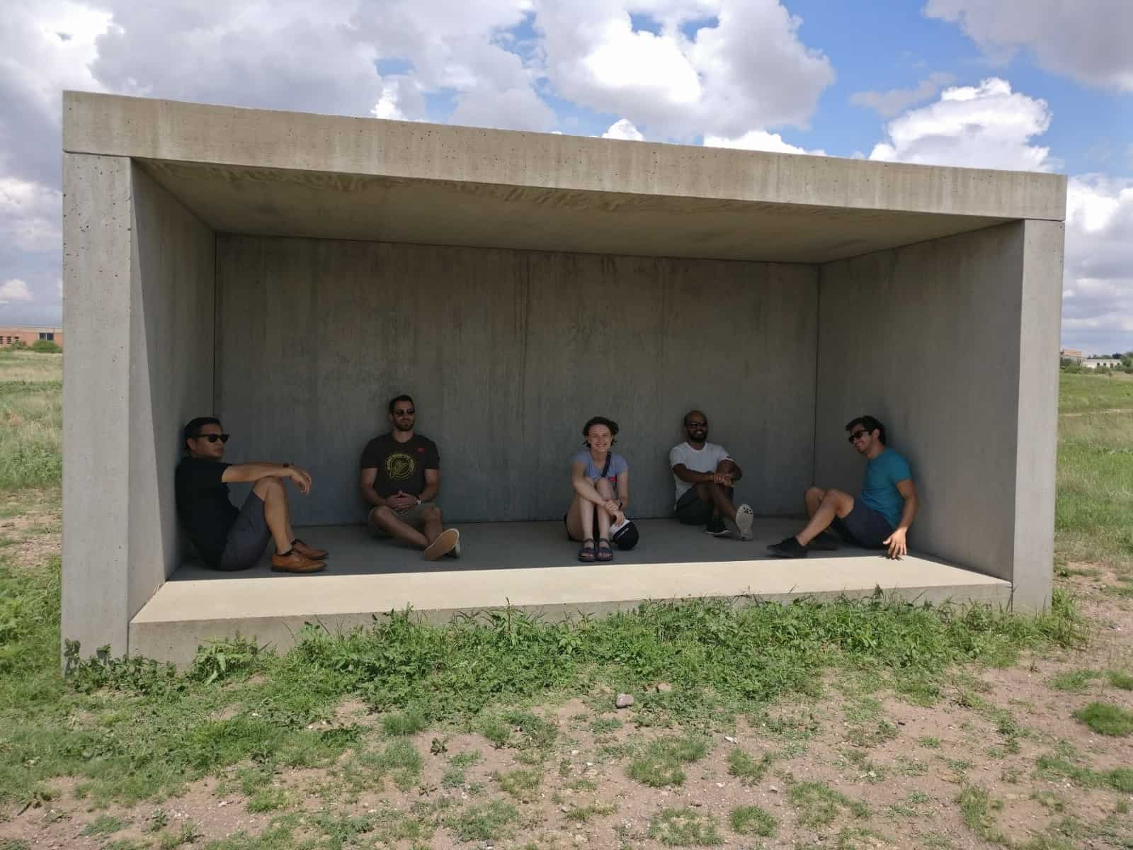 Produktworks team sitting inside a concrete art installation at Chinatti Marfa
