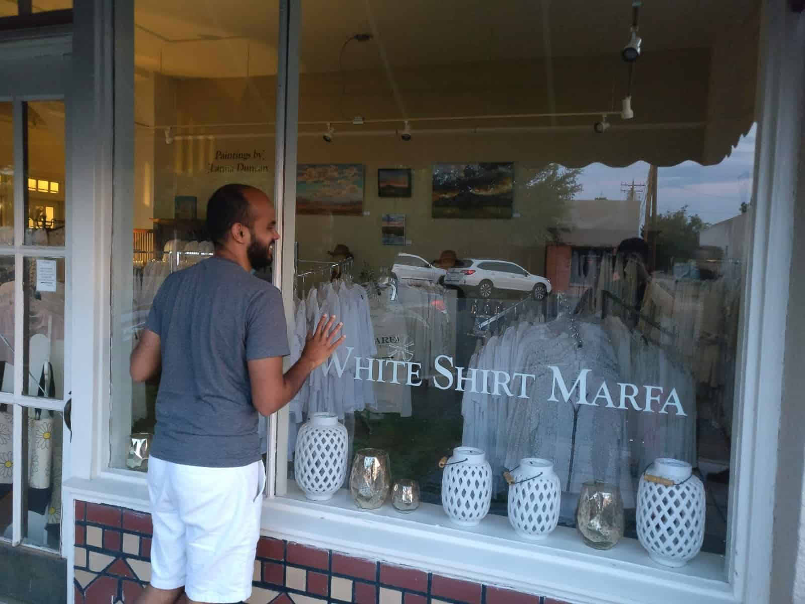 Deepak looking through a store selling white shirts
